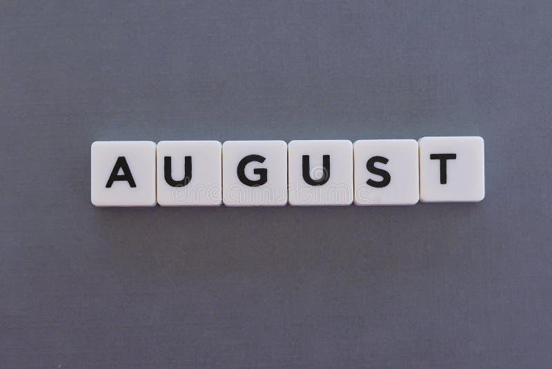 August-Wort gemacht vom quadratischen Buchstabewort auf grauem Hintergrund stockfoto