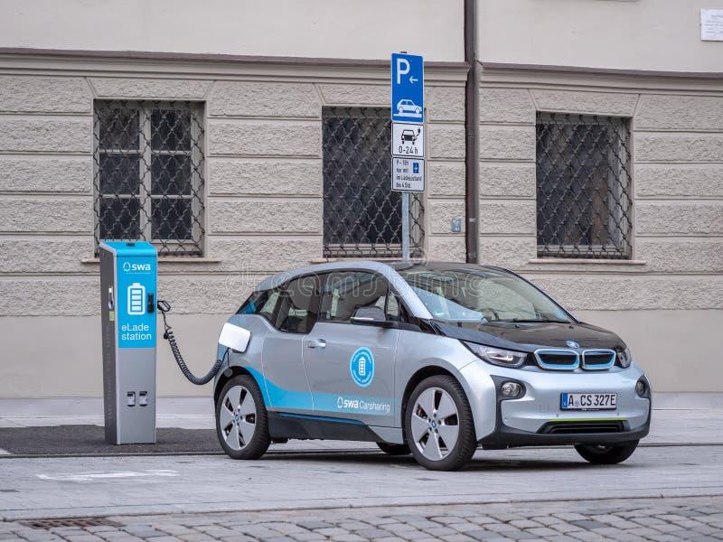 Augusta, Germania - 7 maggio 2019: BMW I3 sta facendo pagare l'elettricità ad una stazione di carico nella città fotografia stock libera da diritti