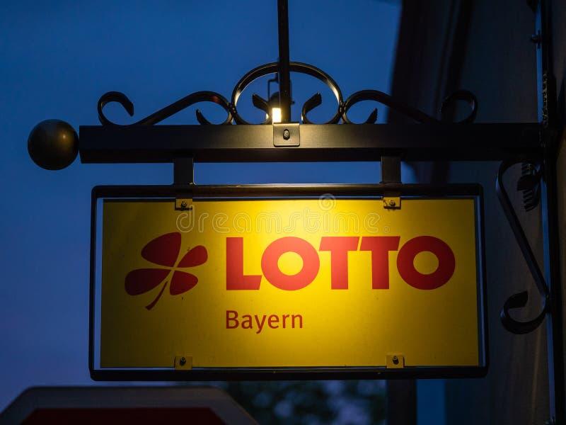 Augusta, Germania - 5 maggio 2019: Immagine del segno giallo illuminato con le lettere rosse del lotto in Baviera immagini stock libere da diritti
