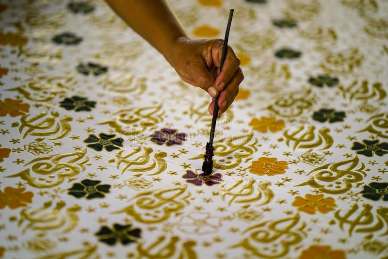 Augusti 11 2019, Surakarta Indonesien: Nära övre hand som gör batik på tyget med att välta med bokehbakgrund royaltyfria bilder