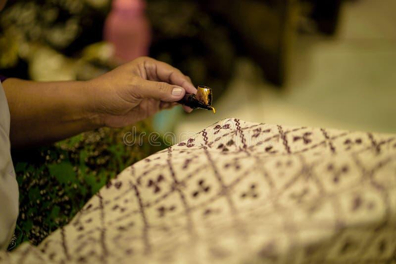 Augusti 11 2019, Surakarta Indonesien: Nära övre hand som gör batik på tyget med att välta med bokehbakgrund arkivbilder