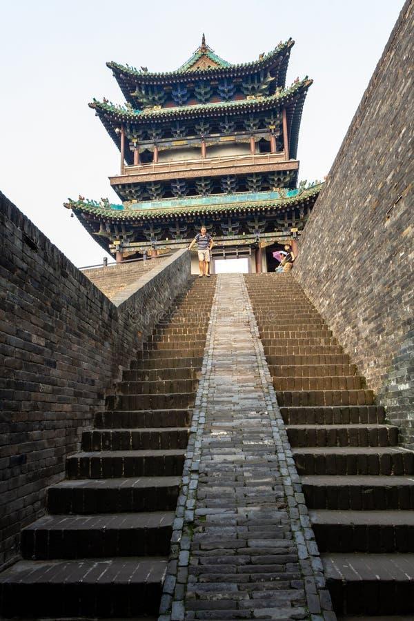 Augustus 2013 - Pingyao, China - Toeristen op de ingangstrap van de oude muren die de Oude stad van Pingyao beschermen stock fotografie