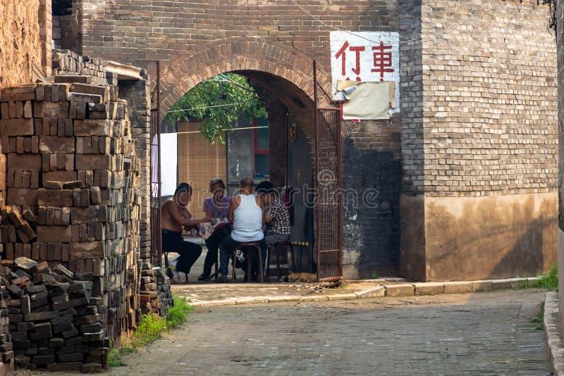 Augustus 2013 - Pingyao, Shanxi, China - Plaatselijke bevolking die in een binnenplaats van de Oude Stad van Pingyao spelen royalty-vrije stock afbeelding