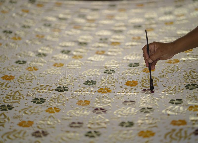 11 augustus 2019, Surakarta Indonesië: Sluit omhoog hand om batik op de stof te maken met het afschuinen met bokehachtergrond stock foto