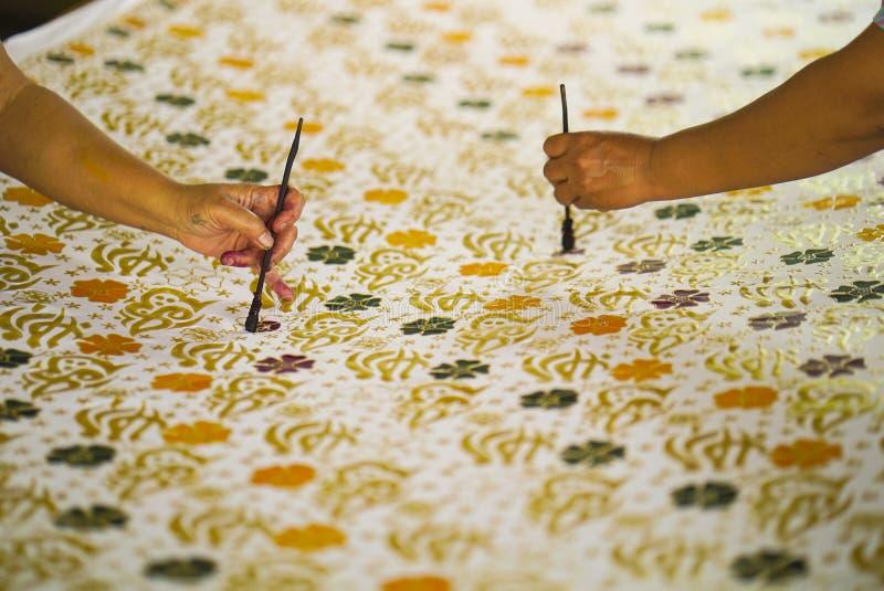 11 augustus 2019, Surakarta Indonesië: Sluit omhoog hand om batik op de stof te maken met het afschuinen met bokehachtergrond stock afbeelding