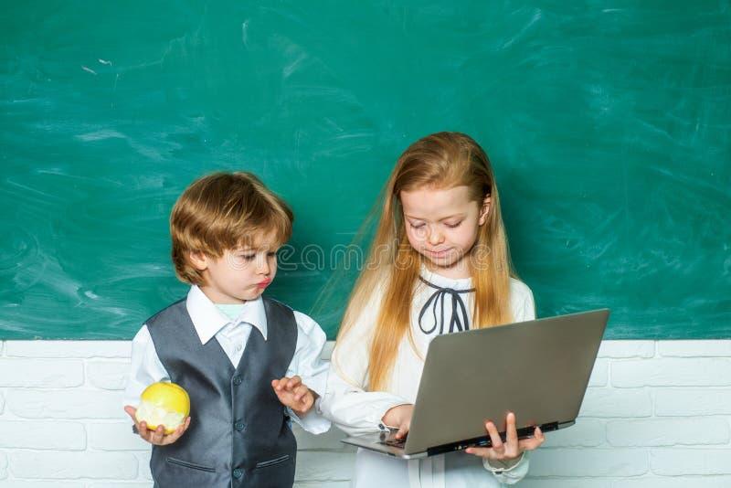 Aula Primo giorno di scuola Bambini d'aiuto di Schoolgirl dell'insegnante con il loro compito in aula a scuola Formazione in prim immagine stock libera da diritti