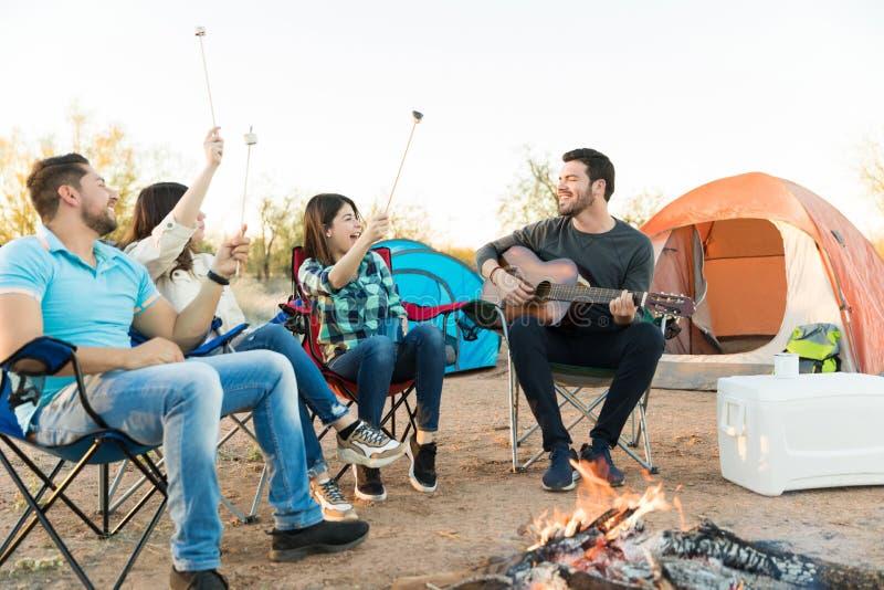 Aumentando marshmallows para apreciar o amigo que joga a guitarra imagens de stock royalty free