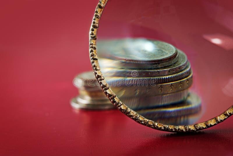 Aumento de capital, lupa delante de un pequeño stac de la moneda imagen de archivo