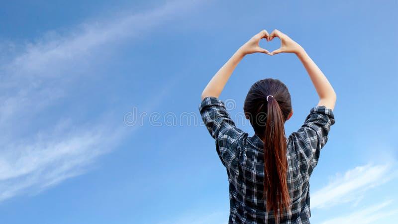 Aumento de la mujer sus manos para hacer forma del corazón en el aire imágenes de archivo libres de regalías