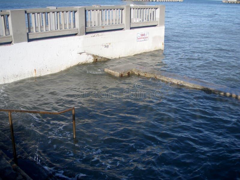Aumento del agua de la marea sobre las escaleras de las tomas fotos de archivo libres de regalías