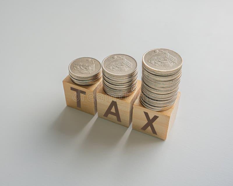 aumento del impuesto sobre la renta con monedas apiladas en cubos de madera sobre una mesa fotos de archivo
