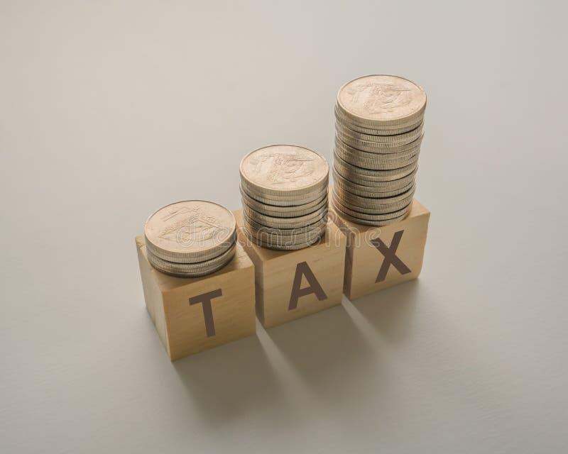 aumento del impuesto sobre la renta con monedas apiladas en cubos de madera sobre una mesa fotografía de archivo libre de regalías