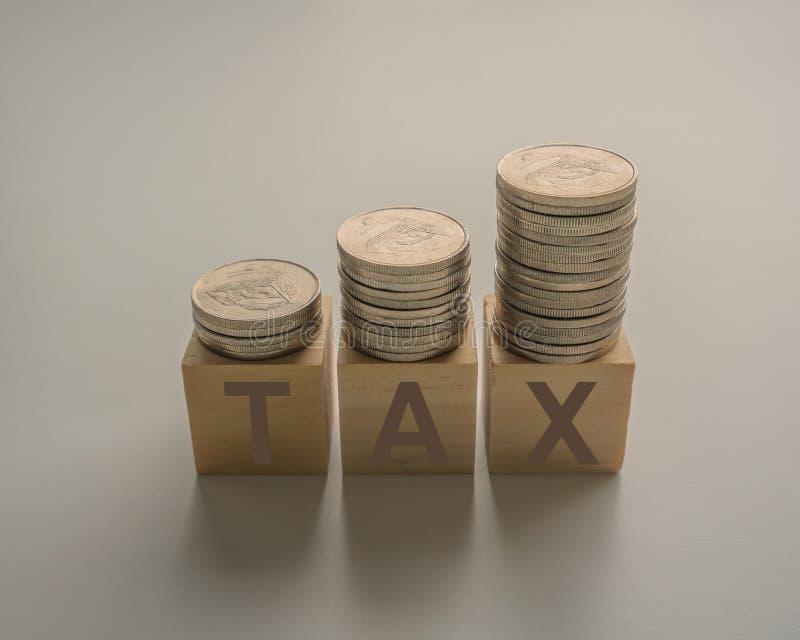 aumento del impuesto sobre la renta con monedas apiladas en cubos de madera sobre una mesa foto de archivo