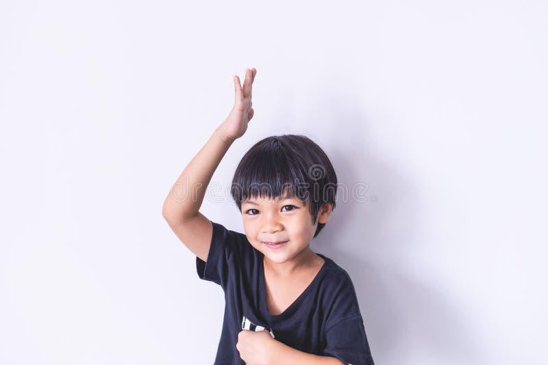 Aumento del muchacho su mano para arriba en el fondo blanco imagen de archivo libre de regalías