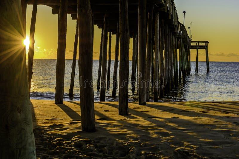 Aumento del sole dell'oceano sotto il pilastro fotografie stock libere da diritti