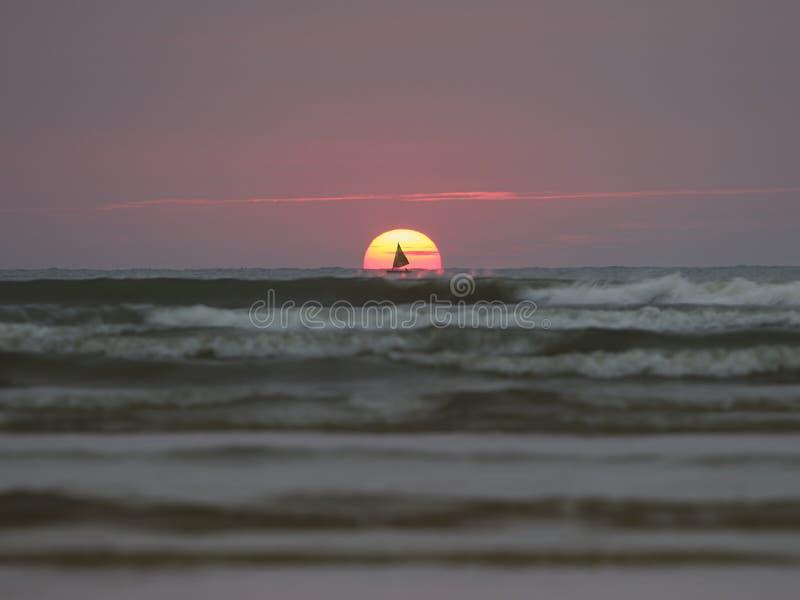 Aumento del sole e della barca a vela nel mare fotografia stock libera da diritti