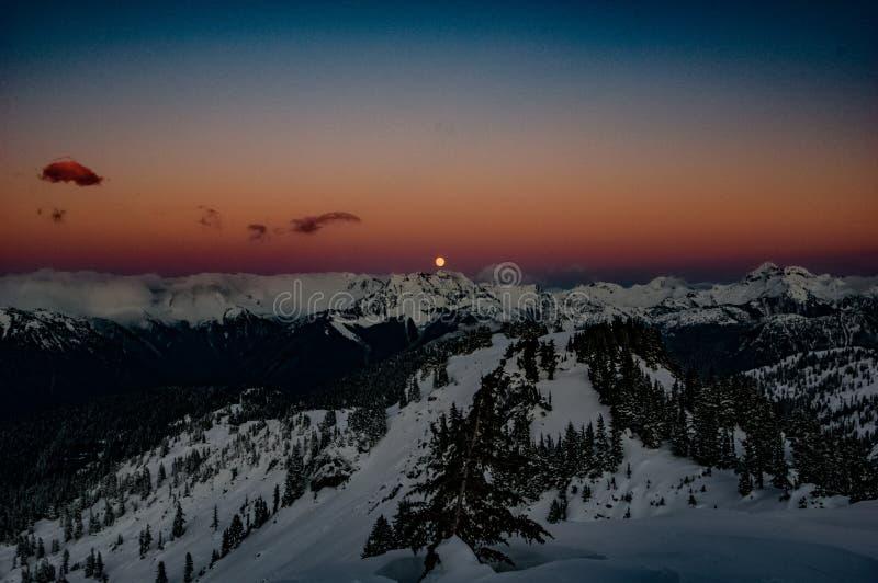 Aumento della luna sopra le montagne della cascata fotografie stock