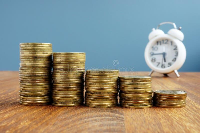 Aumento do crescimento, do investimento e das economias da riqueza Pilhas de moedas e de relógio fotografia de stock