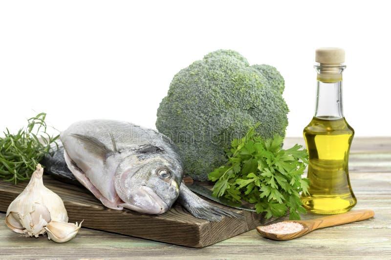 Aurata för fiskhavsbreamsSparus på en skärbräda, en olivolja, en broccoli, en vitlök och aromatiska örter på en trätabellnärbild arkivbilder