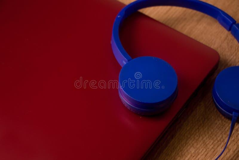 Auriculares azules con el cuaderno rojo imagen de archivo libre de regalías