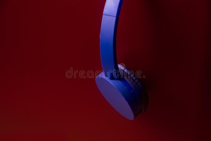 Auriculares azules en fondo rojo foto de archivo libre de regalías