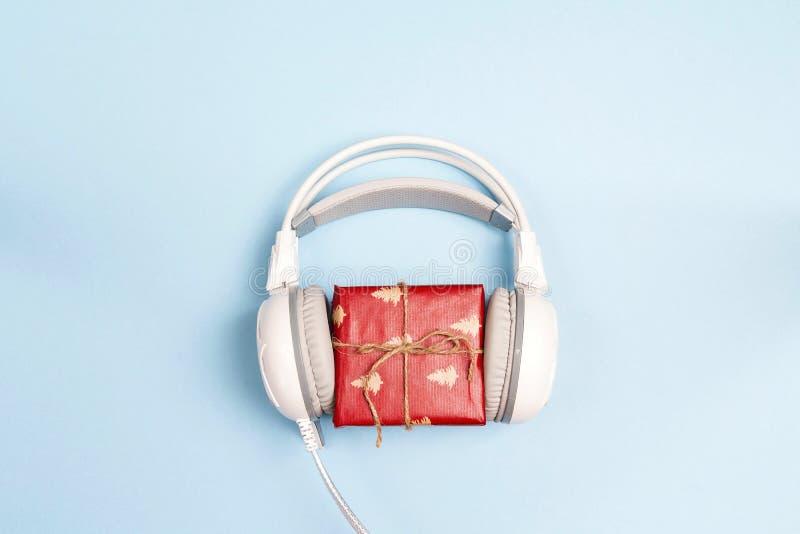 Auriculares blancos con Año Nuevo rojo o caja de regalo de la Navidad en un bl imagen de archivo libre de regalías