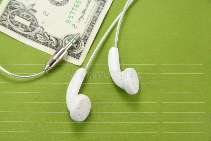 Auriculares blancos con el dólar fotografía de archivo