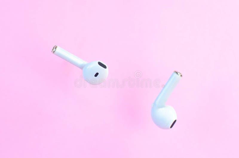 Auriculares blancos sin cuerda en el aire en un fondo rosado foto de archivo libre de regalías
