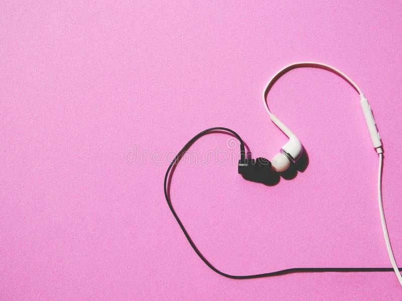 Auriculares blancos y negros con besarse en forma de corazón en fondo rosado imagenes de archivo