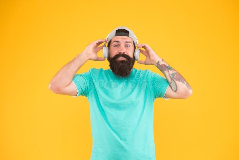 Auriculares com projeto ergonômico Moderno que veste auriculares brancos ajustáveis no fundo amarelo Homem farpado que escuta imagens de stock