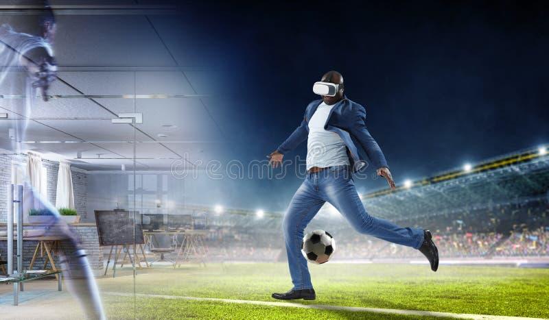 Auriculares de la realidad virtual en un var?n negro que juega a f?tbol fotografía de archivo