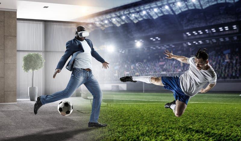Auriculares de la realidad virtual en un var?n negro que juega a f?tbol T?cnicas mixtas imagen de archivo