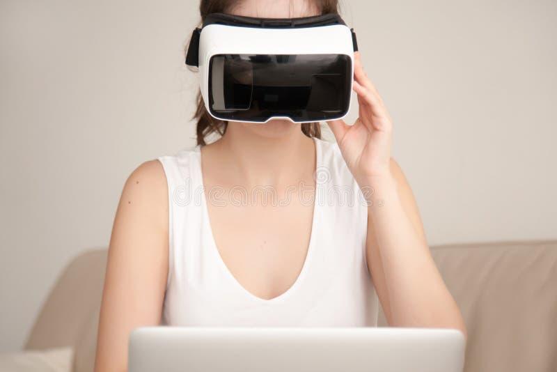 Auriculares de VR para el ordenador portátil, mujer joven que lleva el vidrio de la realidad virtual fotos de archivo libres de regalías