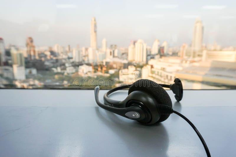 Auriculares del teléfono del IP para el servicio de atención al cliente en la opinión de la ciudad imagen de archivo libre de regalías