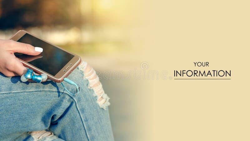 Auriculares del teléfono móvil del smartphone del reloj de la camiseta de los vaqueros de la sentada de la mujer en fondo de la f imagenes de archivo