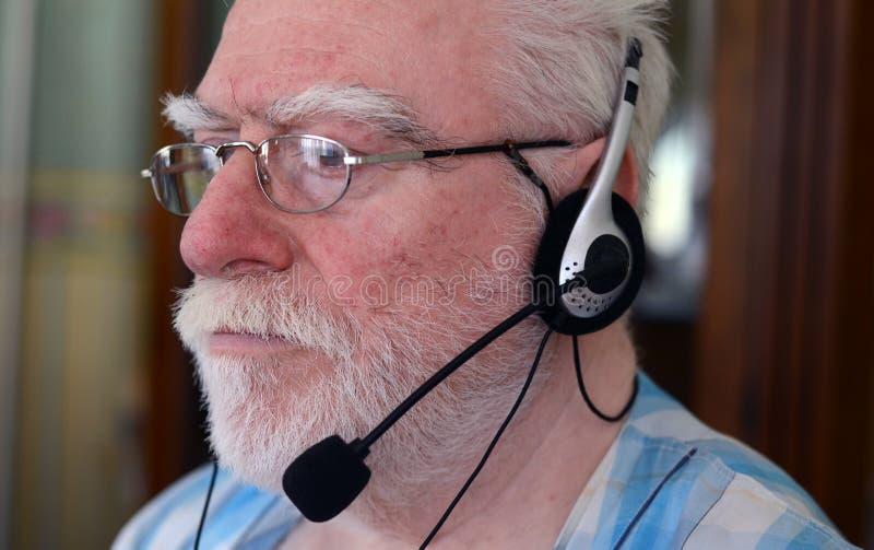 Auriculares desgastando do homem sênior foto de stock royalty free