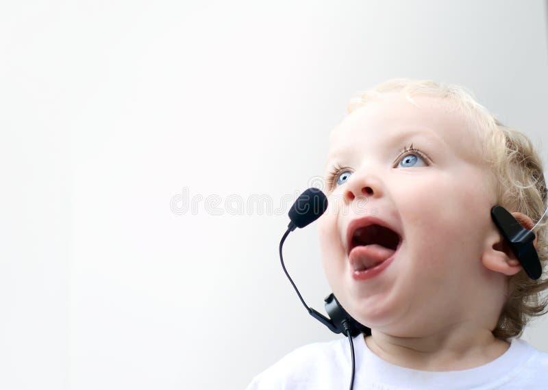 Auriculares desgastando do telefone do menino novo imagem de stock