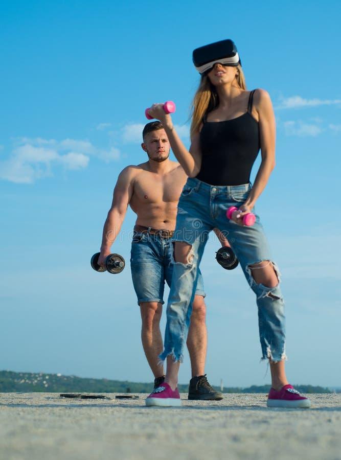 Auriculares do desgaste de mulher VR Simulador do uso do atleta da mulher para treinar Exercício do halterofilista da mulher com  imagens de stock