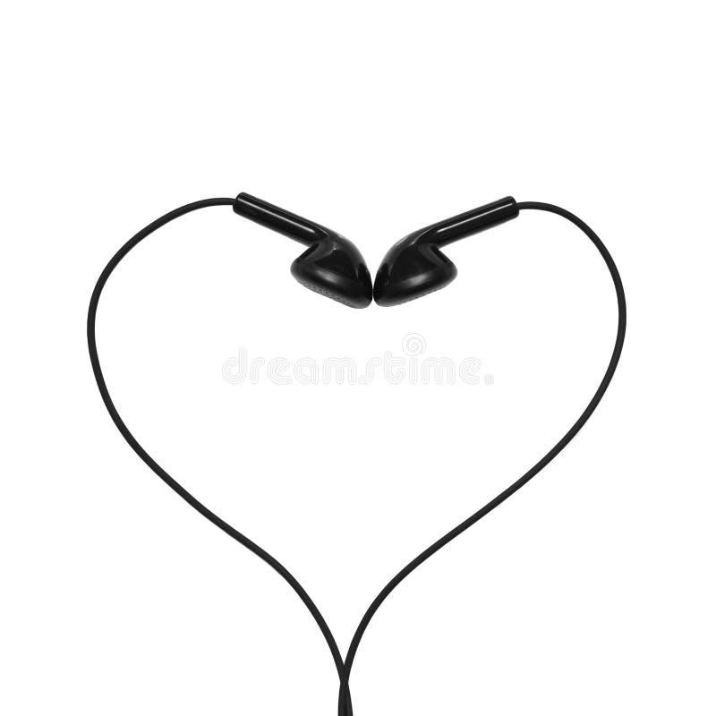 Auriculares doblados bajo la forma de corazón imagenes de archivo
