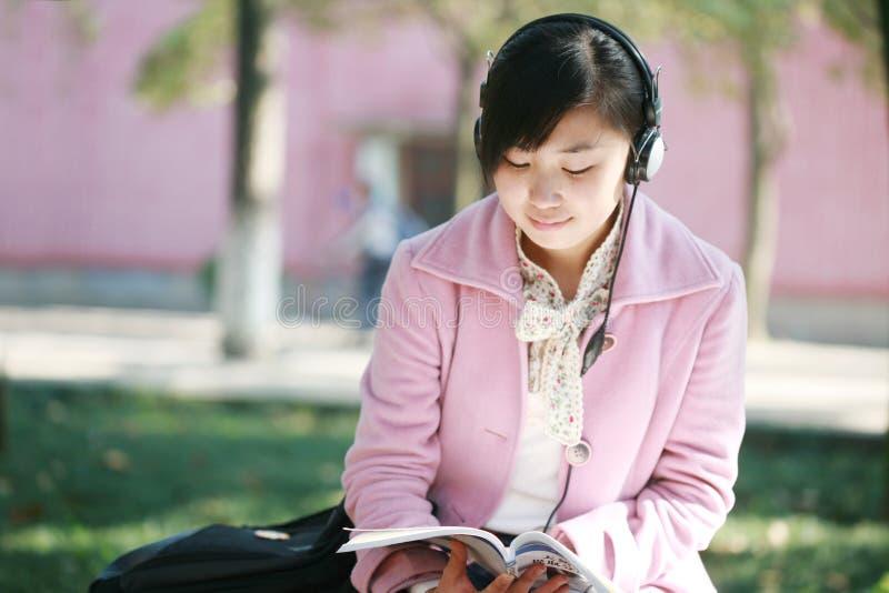 Auriculares e livro da preensão da menina fotografia de stock royalty free