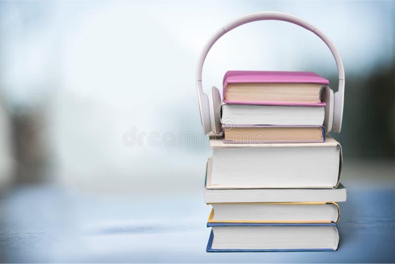 Auriculares en los libros imagen de archivo