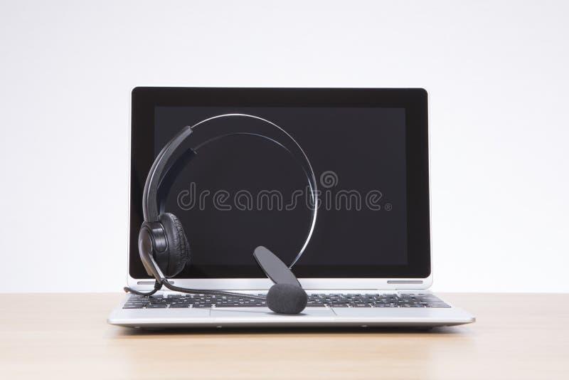 Auriculares en un teclado abierto del ordenador portátil fotografía de archivo libre de regalías