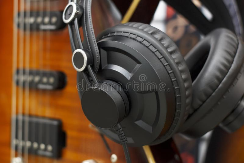 Auriculares estéreos con la guitarra, concepto casero de la grabación de la canción popular, estilo del vintage La música entreti foto de archivo libre de regalías
