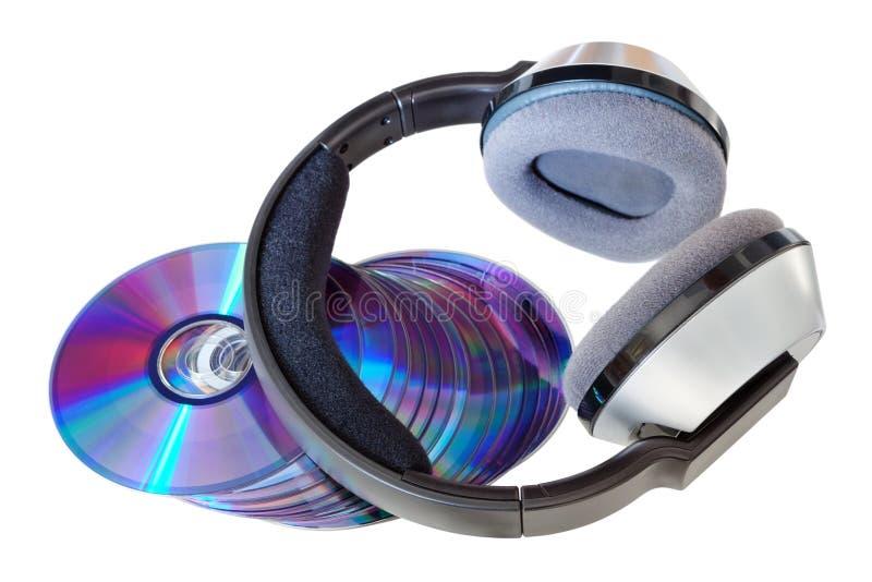 Auriculares inalámbricos modernos en una pila de Cdes y de DVDs. foto de archivo