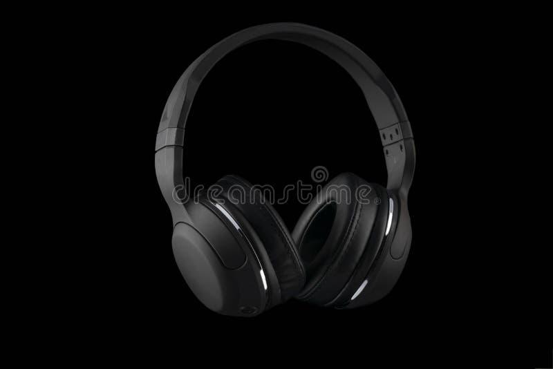 Auriculares inalámbricos negros aislados en un fondo negro imagen de archivo