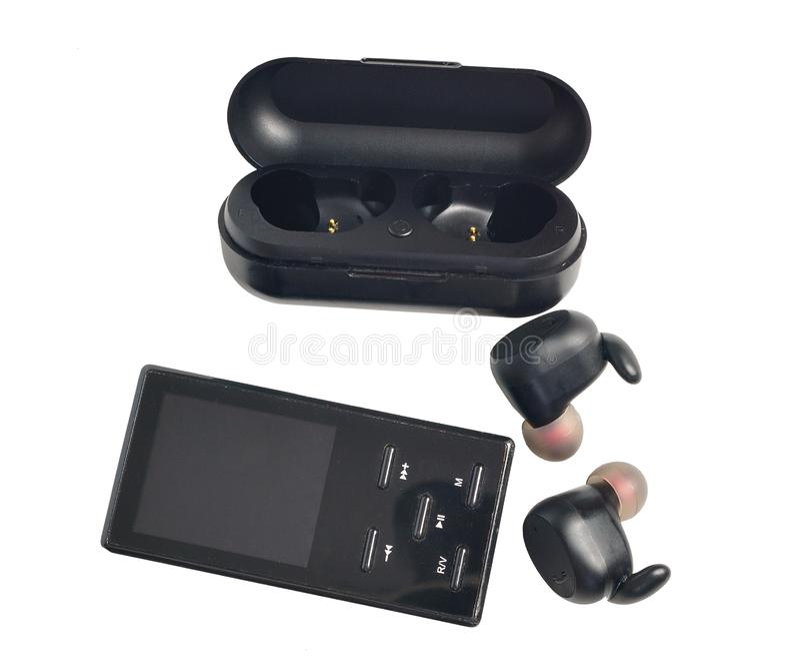 Auriculares inal?mbricos auriculares inalámbricos en el caso de la carga y del pleer mp3 aislados en el fondo blanco foto de archivo libre de regalías
