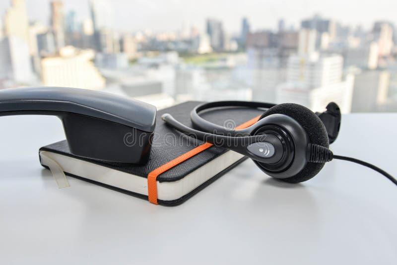 Auriculares - microteléfono de y cuaderno negro imagen de archivo