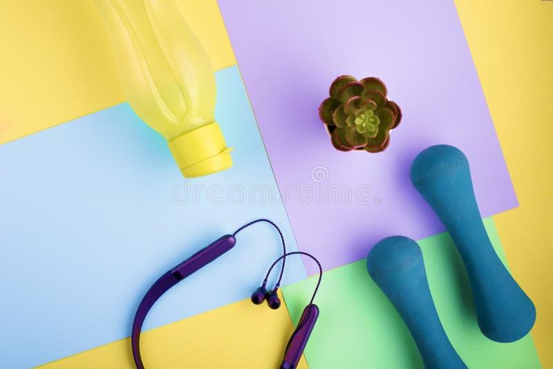 Auriculares modernos, pesas de gimnasia azules, botella de agua amarilla en bloques brillantes del color Concepto de la forma de  imagen de archivo libre de regalías