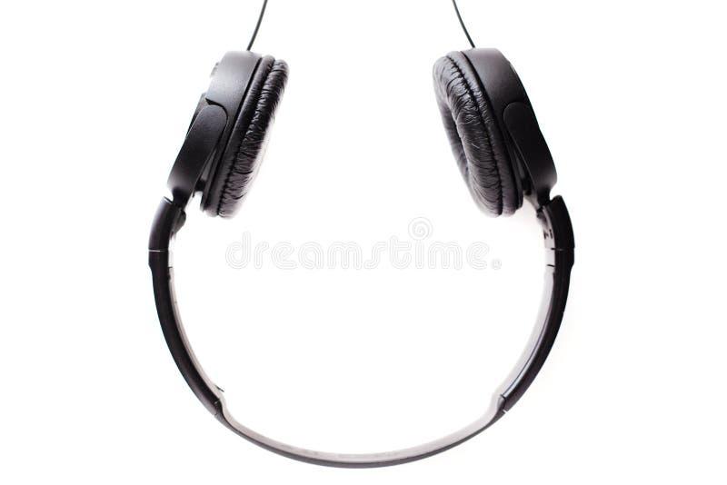 Auriculares negros en un fondo blanco al revés, auriculares izquierdos y derechos con un borde del marco para escuchar la música  imagen de archivo