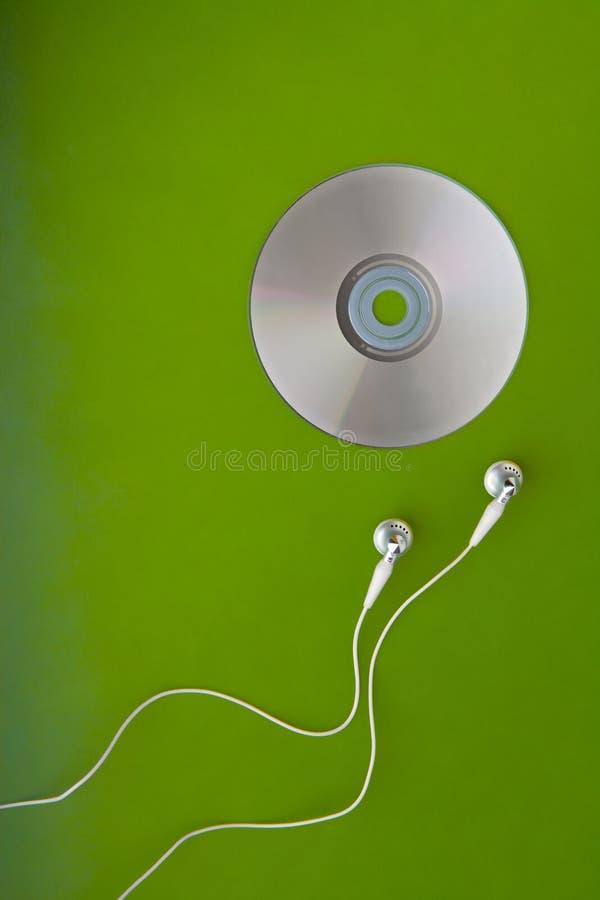 Auriculares o auriculares CD de la música en verde   foto de archivo